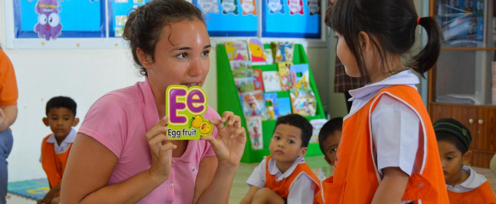A gap year volunteer abroad teaches a child the alphabet in Thailand as part of her Childcare Project.